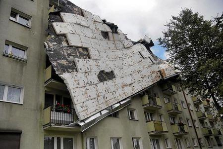 A roof destroyed by a storm hangs from an apartment building in Bydgoszcz