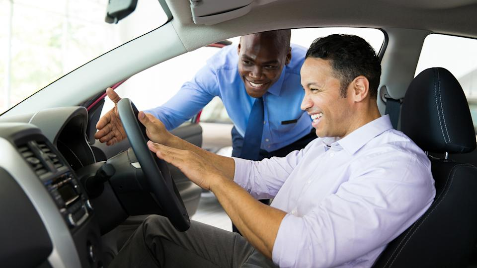 friendly african salesman explaining car features to customer.