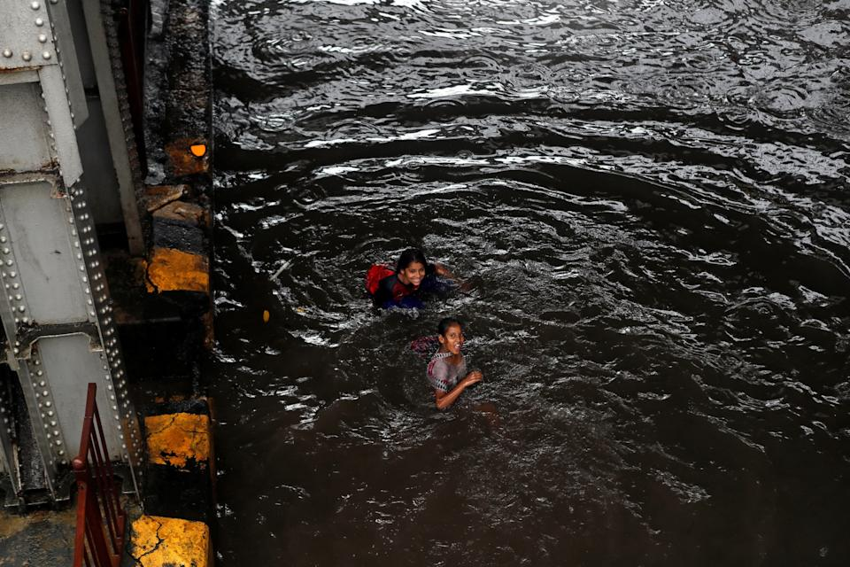 Children play on a waterlogged road after it was closed because of heavy rainfall in Mumbai, India,