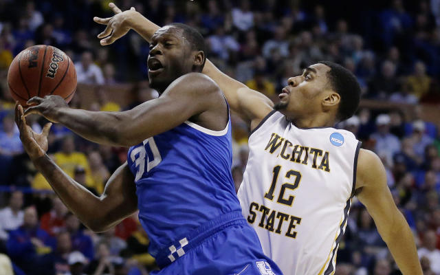 Kentucky forward Julius Randle (30) passes around Wichita State forward Darius Carter (12) during the first half of a third-round game of the NCAA college basketball tournament Sunday, March 23, 2014, in St. Louis. (AP Photo/Jeff Roberson)