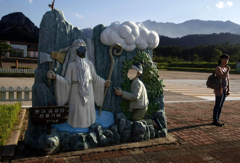 """In this photo taken Wednesday, Aug. 31, 2011, a visitor walks near a souvenir photo stand which depicts a traditional Korean parable about a woodcutter who encounters a mountain spirit with a sign that reads """" Hyundai Mt Kumgang souvenir - Fuji film """" in the mostly shuttered retail area of the Mount Kumgang resort, also known as Diamond Mountain,  in North Korea.  South Korea is asking foreign governments to ignore North Korea's push to open the tourist resort the Koreas once ran jointly to international investors.  (AP Photo/Ng Han Guan)"""