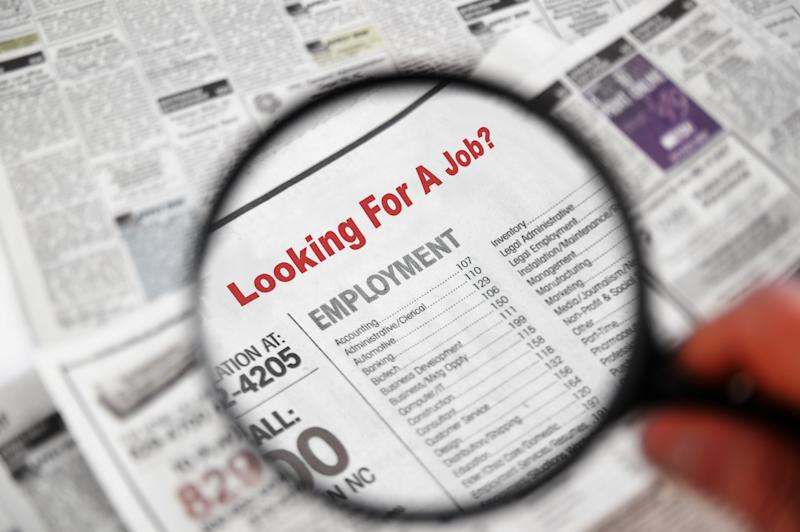 Magnifying glass over Jobs section of newspaper classifieds