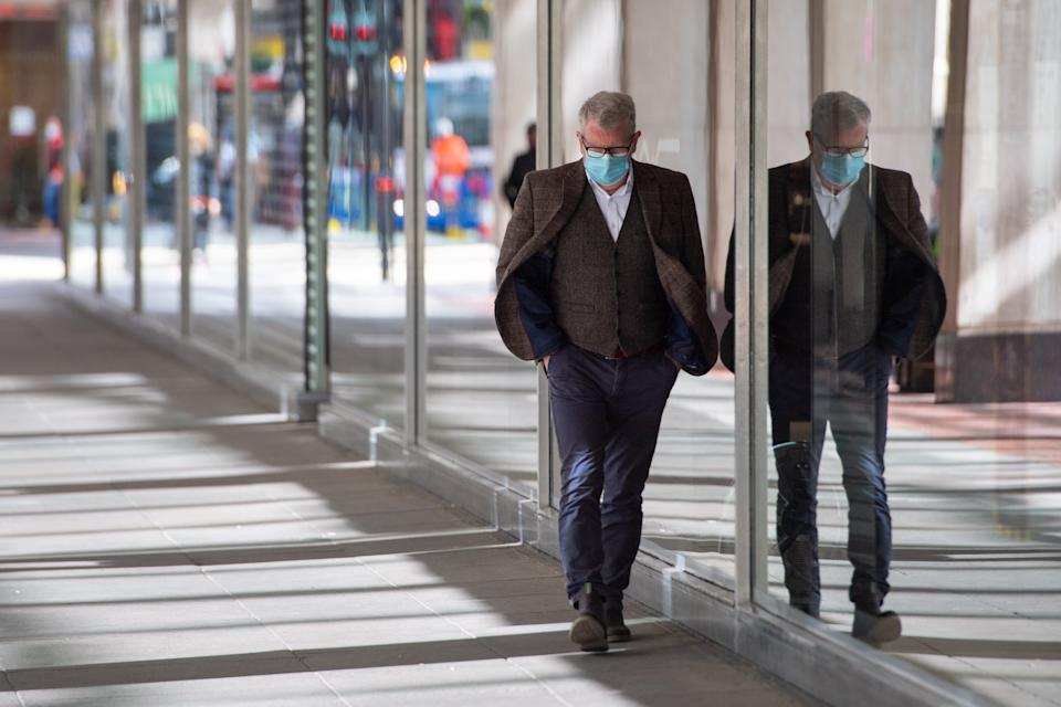 A man wearing a protective face mask passes closed non-essential shops in central London, as England continues to ease coronavirus restrictions. Picture date: Tuesday April 6, 2021. Prime Minister Boris Johnson faces a battle over plans to introduce �vaccine passports� for people to demonstrate their Covid-19 status, using a smartphone app.