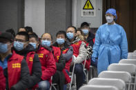 A medical worker wearing protective equipment monitors patients after they received the coronavirus vaccine at a vaccination facility in Beijing, Friday, Jan. 15, 2021. A city in northern China is building a 3,000-unit quarantine facility to deal with an anticipated overflow of patients as COVID-19 cases rise ahead of the Lunar New Year travel rush. (AP Photo/Mark Schiefelbein)