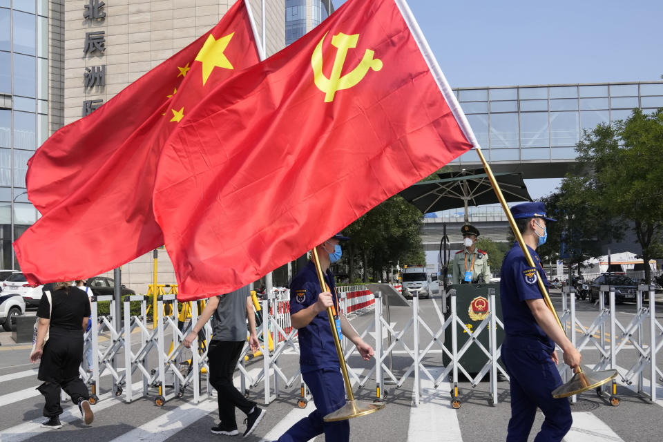 Security personnel holding the Communist Party and Chinese national flags prepare to enter the venue for the China International Fair for Trade in Services (CIFTIS) in Beijing on China, Thursday, Sept. 2, 2021. Chinese and foreign enterprises are expected to showcase their latest technology and services during the annual China International Fair for Trade in Services this week. (AP Photo/Ng Han Guan)