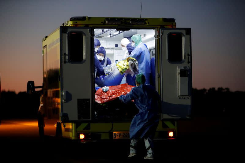Medical staff members move a patient from a plane during a transfer operation of people suffering from the coronavirus disease