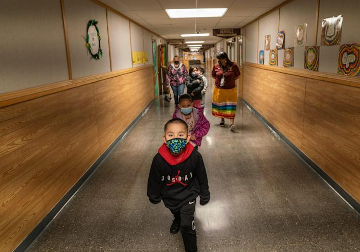 Teacher Shari Daniels, right, walks with her kindergarten class at Poplar Elementary School in mid-March. Daniels attended the school herself as a kid growing up on the neighboring Fort Peck Reservation.