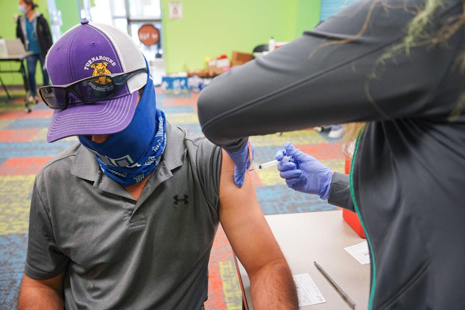 A healthcare vaccinates a man with the Covid-19 vaccine on April 30, 2021,as the Pasadena Public Library hosts a mobile vaccine clinic set up by the Harris County Public Health, in Pasadena, Texas. (Cecile Clocheret/AFP via Getty Images)