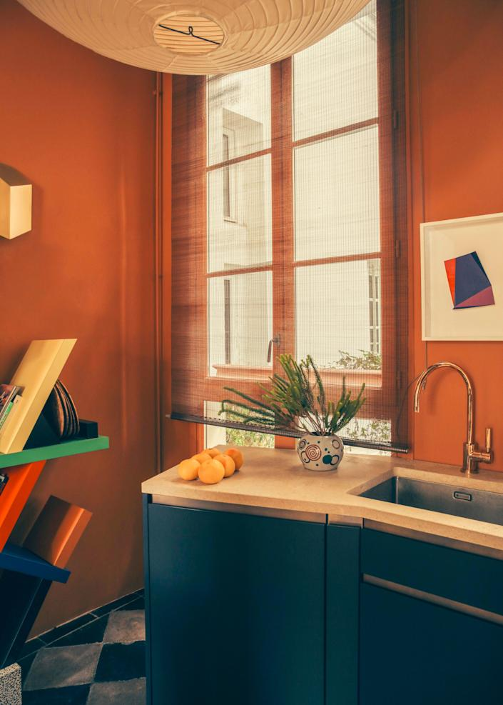 """<div class=""""caption""""> Champsaur, who likes to mix things up, placed a bookshelf by Ettore Sottsass in the kitchen with a Noguchi lantern overhead. </div>"""