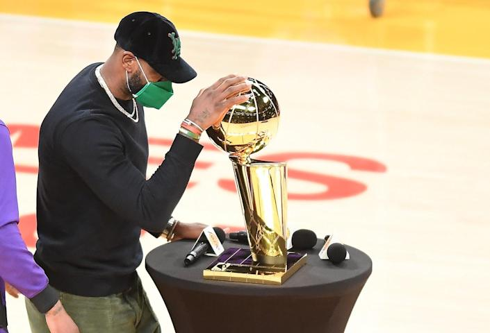 Lakers star LeBron James places his hand on the Larry O'Brien Trophy.