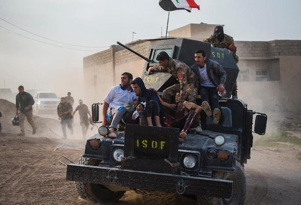 Iraqi soldiers and family rush 12-year-old Mohammed (C-R) and 15-year-old Shafiq (C-L) to an outdoor field clinic on their Humvee in the Al-Samah neighbourhood in Mosul on November 13, 2016 after a double-barreled mortar attack (AFP Photo/Odd Andersen)