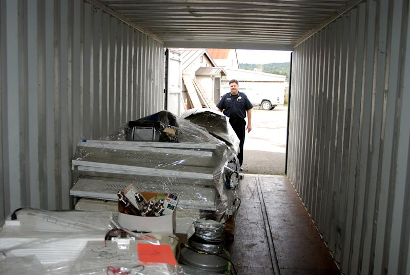 This Oct 24, 2012 photo from Arcata Police Department shows Chief Tom Chapman standing with a shipping container loaded with gear confiscated from illegal marijuana indoor growing operations. Fed up with the proliferation of industrial-scale indooer growing operations taking over homes in residential neighborhoods, city leaders are asking voters to approve a measure to impose a stiff new tax on excessive electricity use, designed to drive large growers out of town. (AP Photo/Arcata Police Department)
