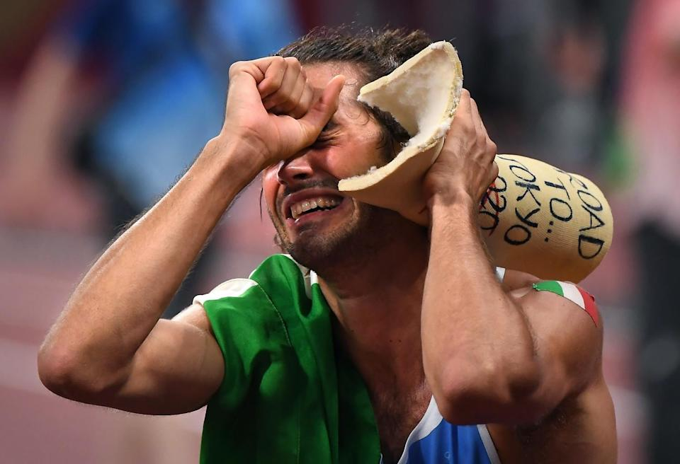 Italy's Gianmarco Tamberi celebrates his gold medal in the high jump by holding a cast from an ankle injury.