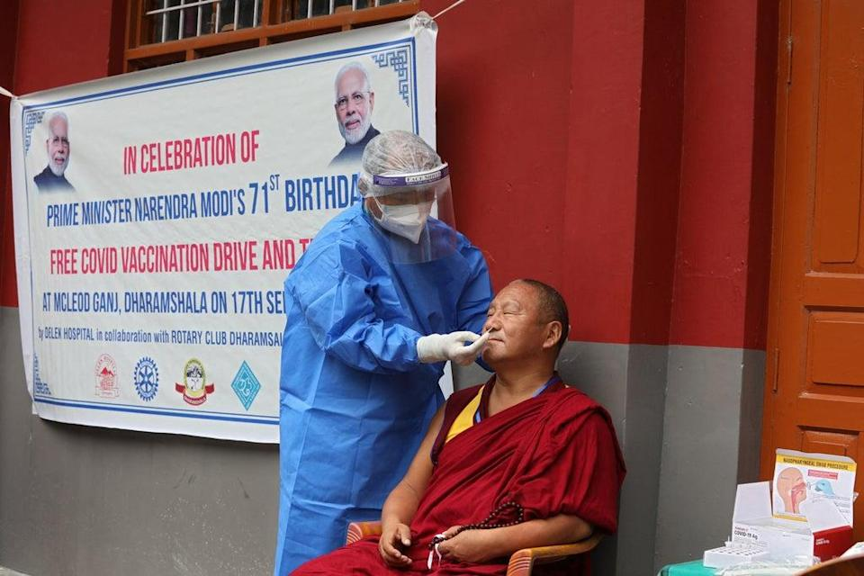 A health worker takes a nasal swab sample from a Tibetan monk in India at a free Covid vaccination and testing drive organised to mark Indian prime minister Narendra Modi's 71st birthday (Getty Images)