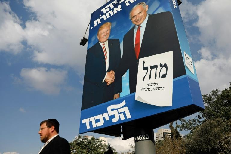 An Israeli man walks past an election billboard in Jerusalem for the Likud party showing US President Donald Trump shaking hands with Prime Minister Benjamin Netanyahu