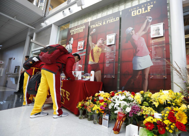 An Iowa State cheerleader signs a memorial card to honor slain student Celia Barquin Arozamena, seen in photo at right, before an NCAA college football game between Iowa State and Akron, Saturday, Sept. 22, 2018, in Ames, Iowa. Barquin, who was the 2018 Big 12 women's golf champion and Iowa State Female Athlete of the Year, was found Monday morning in a pond at a golf course near the Iowa State campus. (AP Photo/Charlie Neibergall)