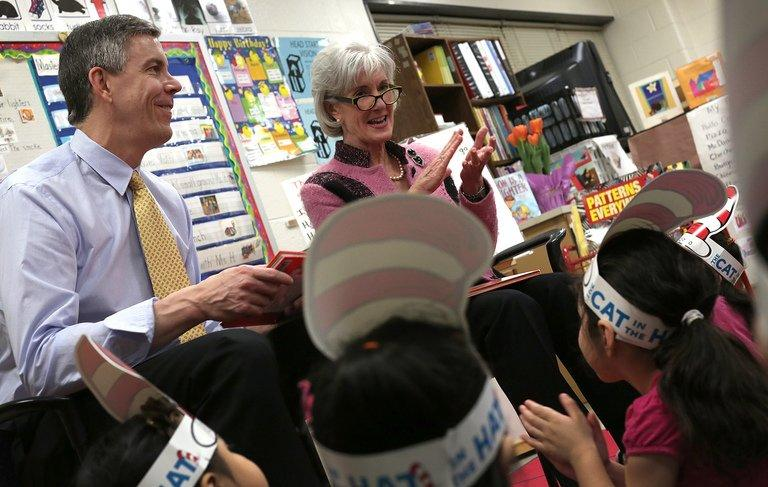 "Education Secretary Arne Duncan (L) and HHS Secretary Kathleen Sebelius (R) read the Dr. Seuss book ""Green Eggs and Ham"" to students enrolled on March 1, 2013 in Takoma Park, Maryland"