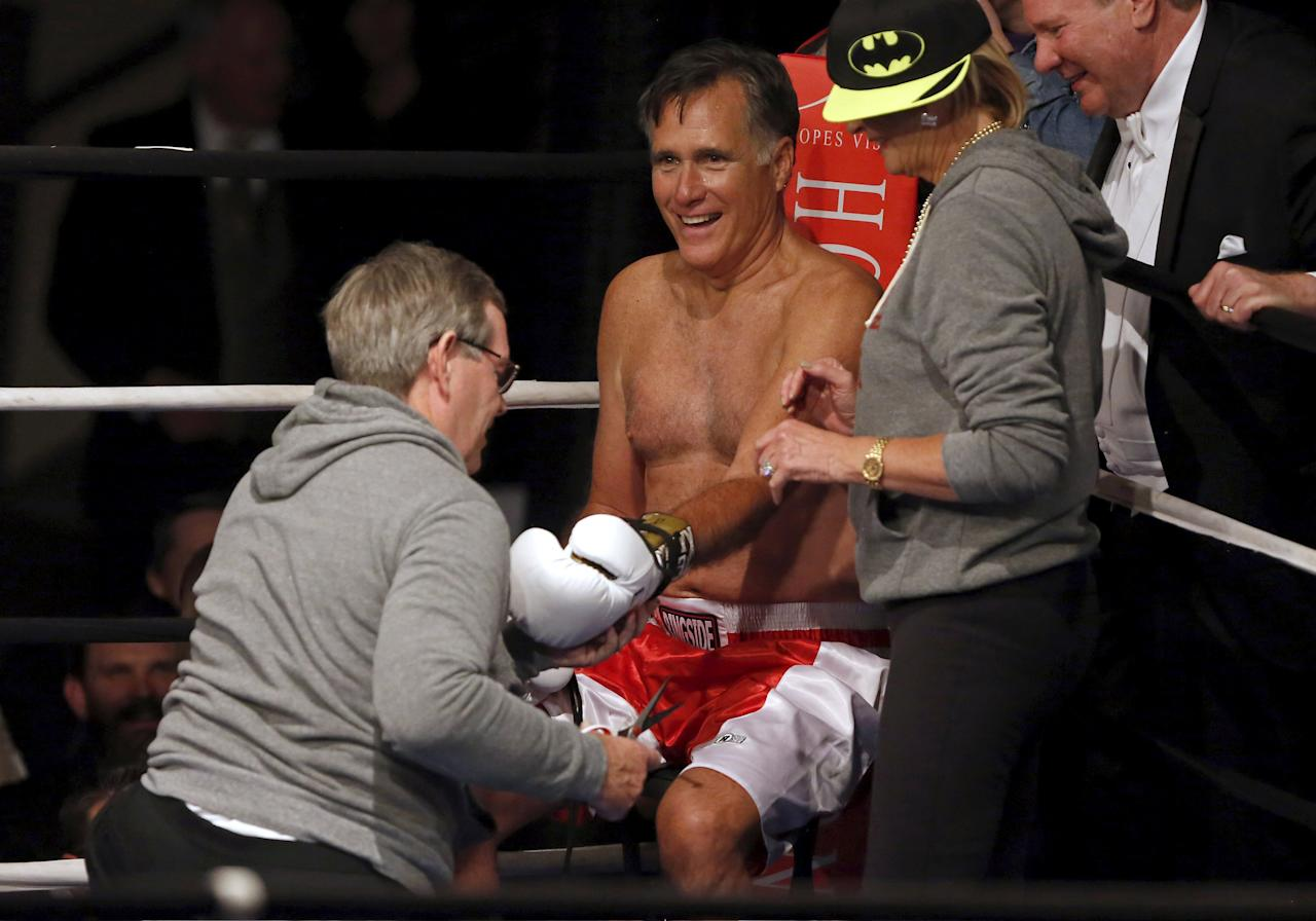 Former Massachusetts Governor and two-time presidential candidate Mitt Romney is tended to in the corner of the ring by his wife Ann Romney (R) and former Utah Governor Mike Leavitt (L) as he fights five-time heavyweight champion Evander Holyfield during a boxing match in Salt Lake City, Utah May 15, 2015. The two boxed to benefit the medical charity CharityVision. REUTERS/Jim Urquhart