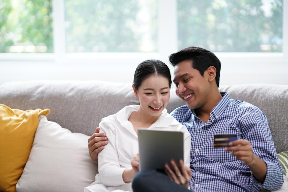 Portrait of Young Asian Couple relaxing in living room using tablet shopping online simple lifestyle in modern family