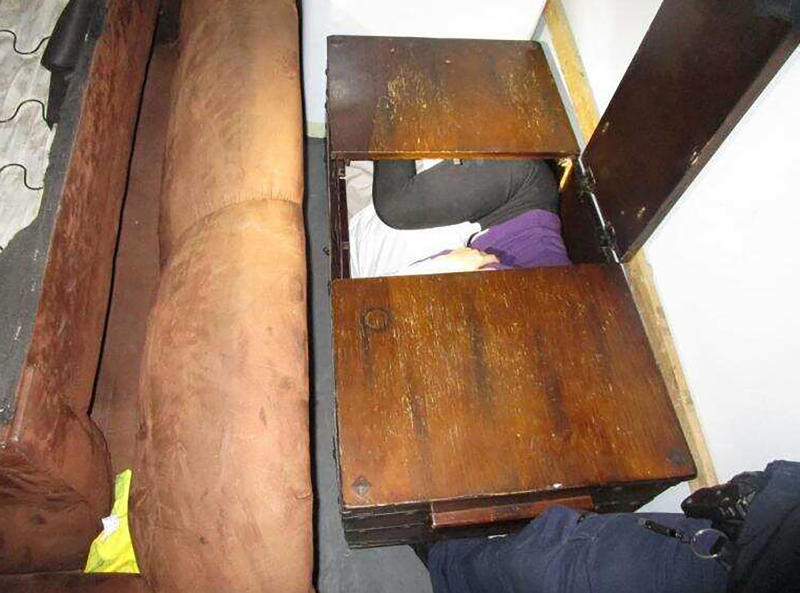 This photo released Monday, Dec. 9, 2019 by U.S. Customs and Border Protection (CBP) shows a person hiding inside a wooden chest, among 11 Chinese nationals found by CBP agents hiding in furniture and appliances inside a moving truck stopped Saturday, Dec. 7, while entering the U.S. from Mexico at the San Ysidro border crossing near San Diego, federal officials said. The truck driver, a 42-year-old U.S. citizen, was arrested on suspicion of human smuggling, according to a statement. (U.S. Customs and Border Protection via AP)