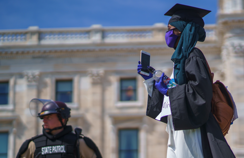 A demonstrator in her graduate outfit walks by Minnesota State Patrol and National Guards standing outside of the state capital building on May 31, 2020 in Saint Paul, Minnesota. (Photo: KEREM YUCEL/AFP via Getty Images)