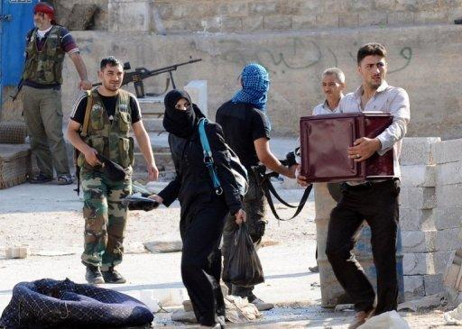 """Syrian civilians carry their belongings as they flee clashes between the Syrian opposition and forces loyal to President Bashar al-Assad, in the center of Syria's restive northern city of Aleppo on July 25. Fighting raged in Syria's second city on Thursday as troops and rebels prepared for a head-on confrontation and pro-regime media warned of a looming """"mother of all battles."""""""