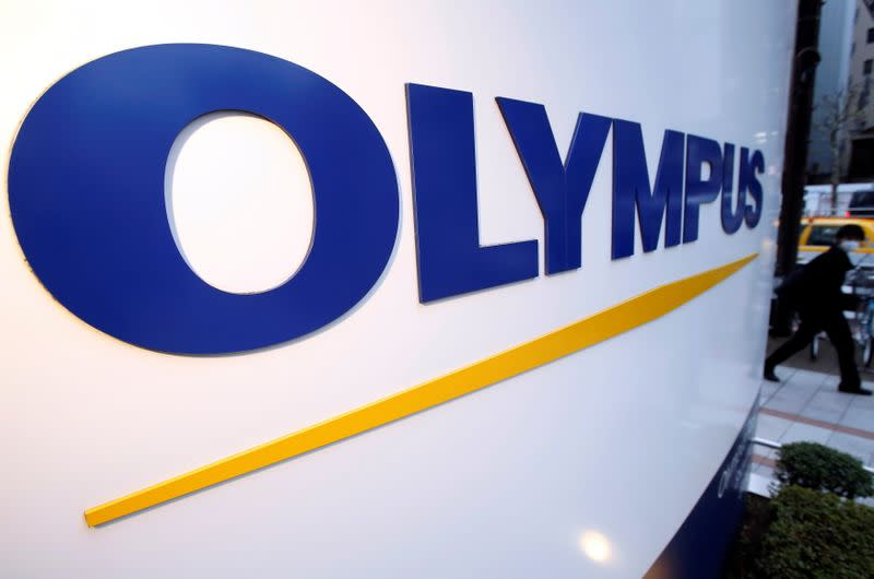 FILE PHOTO: A man passes a logo of Japan's Olympus outside the company showroom in Tokyo