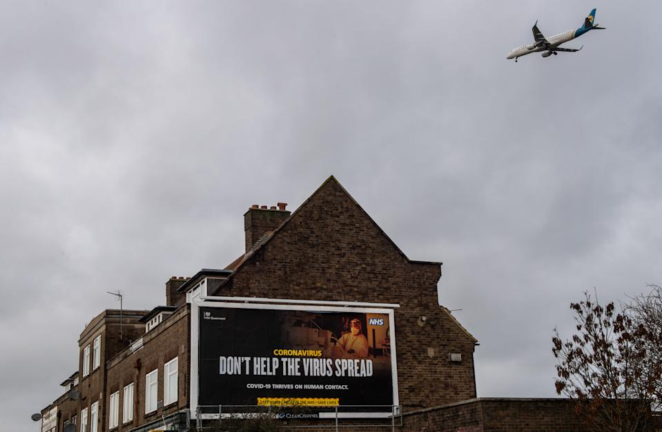 LONDON, ENGLAND - JANUARY 28: An airplane flies over a billboard displaying government coronavirus messaging as it comes in to land at Heathrow Airport on January 28, 2021 in London, England. Arriving travellers from 22
