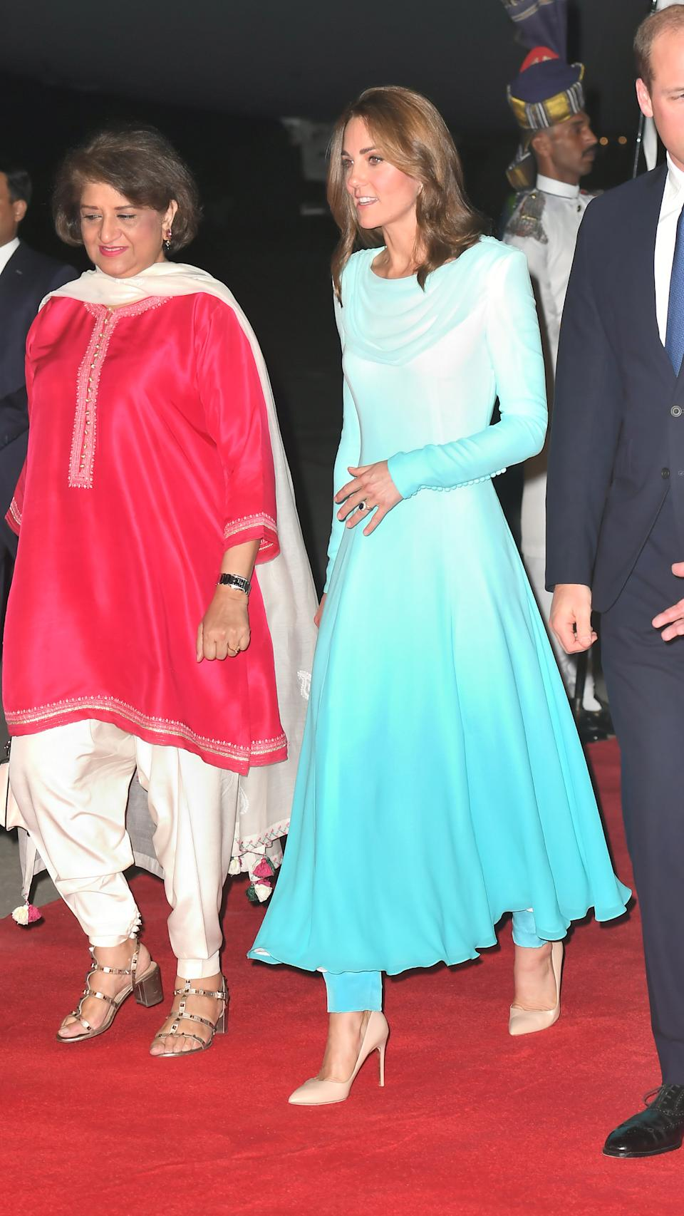 Kate wore an ombre, traditional shalwar kameez by the late Princess Diana's go-to designer for her arrival in Pakistan. A pair of nude Russell & Bromley heels finished the outfit. <em>[Photo: Getty]</em>