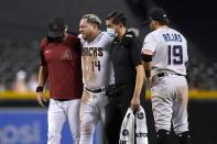 An injured Arizona Diamondbacks' Asdrubal Cabrera (14) grimaces as he is helped off the field by manager Torey Lovullo, left, and assistant athletic trainer Ryne Eubanks, second from right, as Miami Marlins shortstop Miguel Rojas (19) stands nearby during the sixth inning of a baseball game Thursday, May 13, 2021, in Phoenix. (AP Photo/Ross D. Franklin)