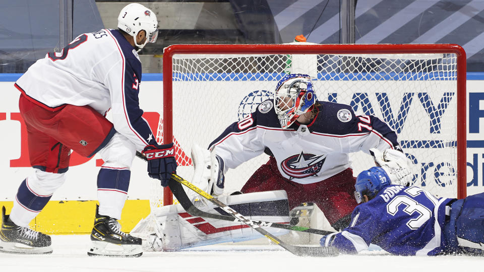 TORONTO, ONTARIO - AUGUST 11: Seth Jones #3 watches as goaltender Joonas Korpisalo #70 of the Columbus Blue Jackets makes a save on Yanni Gourde #37 of the Tampa Bay Lightning during the third overtime of Game One of the Eastern Conference First Round of the 2020 NHL Stanley Cup Playoff at Scotiabank Arena on August 11, 2020 in Toronto, Ontario. (Photo by Mark Blinch/NHLI via Getty Images)