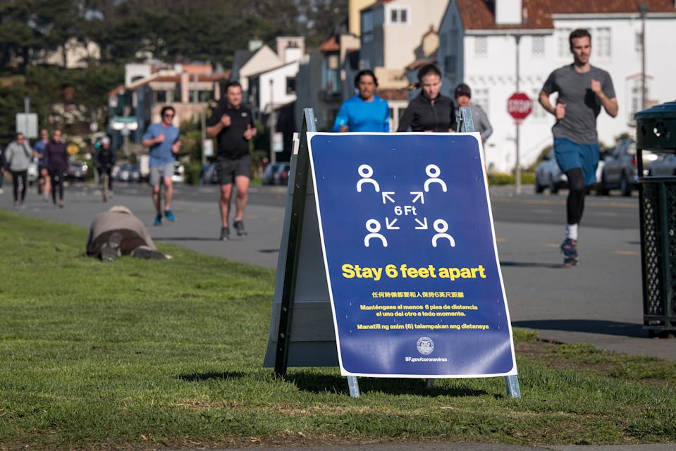 A sign informing people to stay 6 feet apart stands on Marina Boulevard at Marina Green in San Francisco, California on March 25, 2020. (David Paul Morris/Bloomberg via Getty Images)