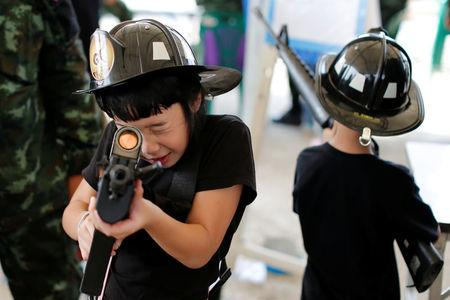 Children play with weapons during Children's Day celebration at a military facility in Bangkok, Thailand January 14, 2017. REUTERS/Jorge Silva