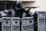 A policeman aims his weapon towards anti-government protesters during clashes near the Government House in Bangkok February 18, 2014. A Thai police officer was killed and dozens of police and anti-government protesters were wounded in gun battles and clashes in Bangkok on Tuesday, officials and witnesses said. REUTERS/Damir Sagolj (THAILAND - Tags: SOCIETY CIVIL UNREST POLITICS)