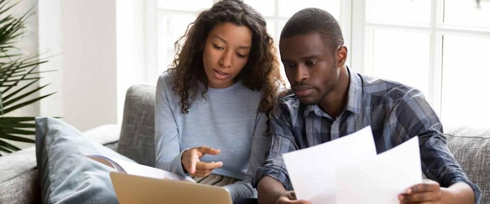 couple discussing paper documents, sitting together on couch at home, in front of computer