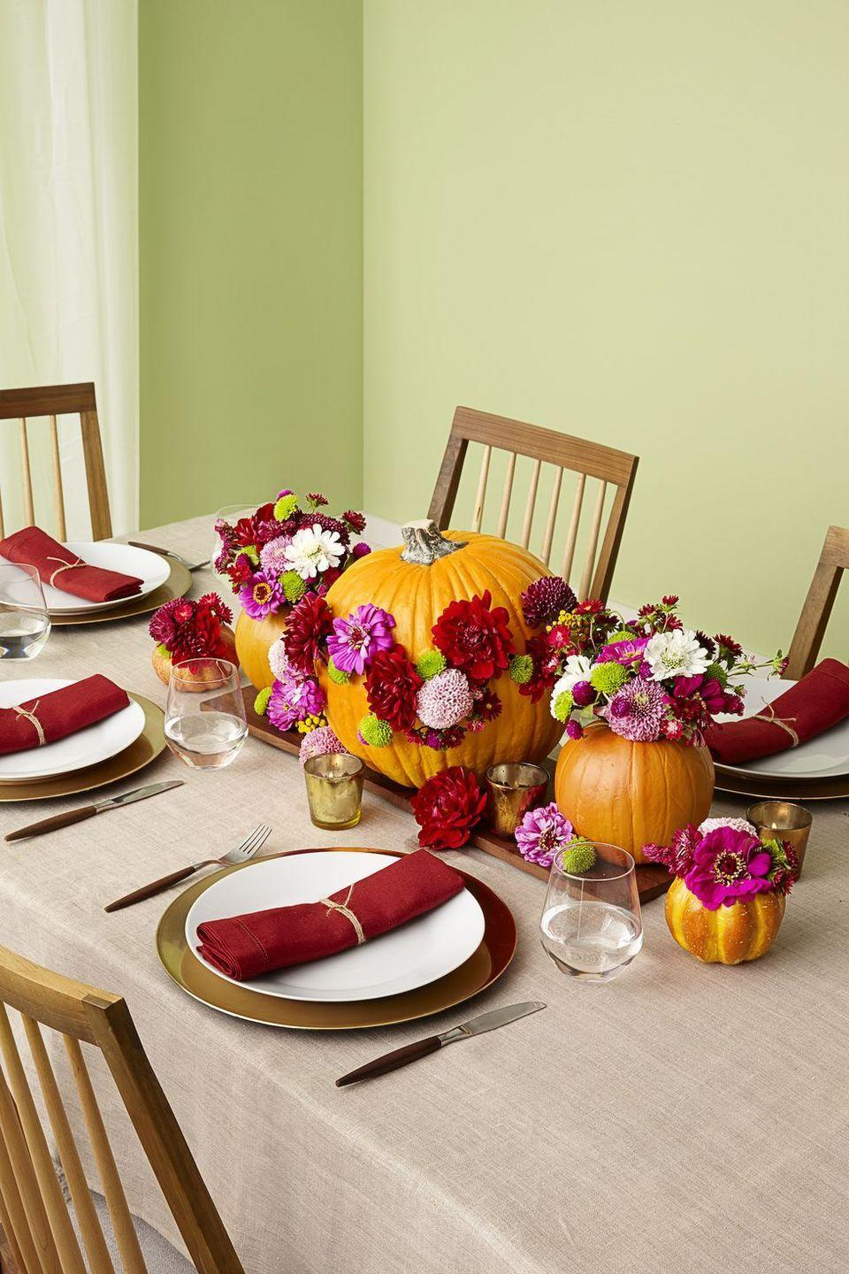 <p>Apply faux flowers to an orange pumpkin to create an inspiring table centerpiece. Finish the design with small pumpkin vases filled with the same flowers.<br></p>