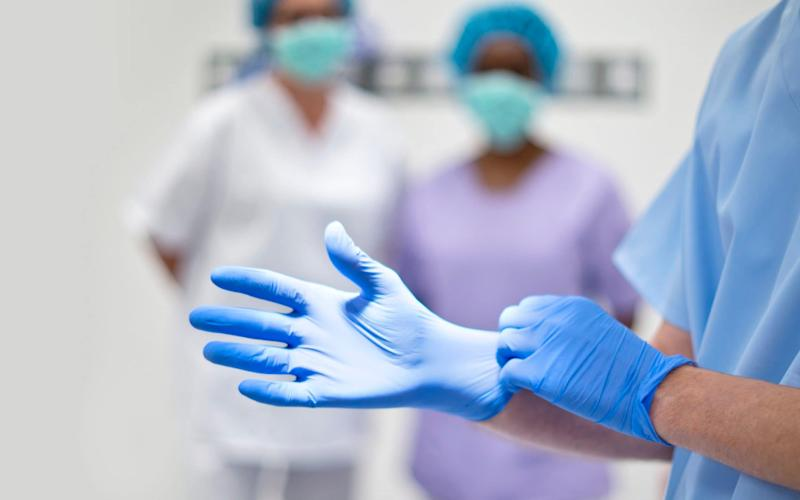 Surgeon putting on latex glove - Science Photo Library