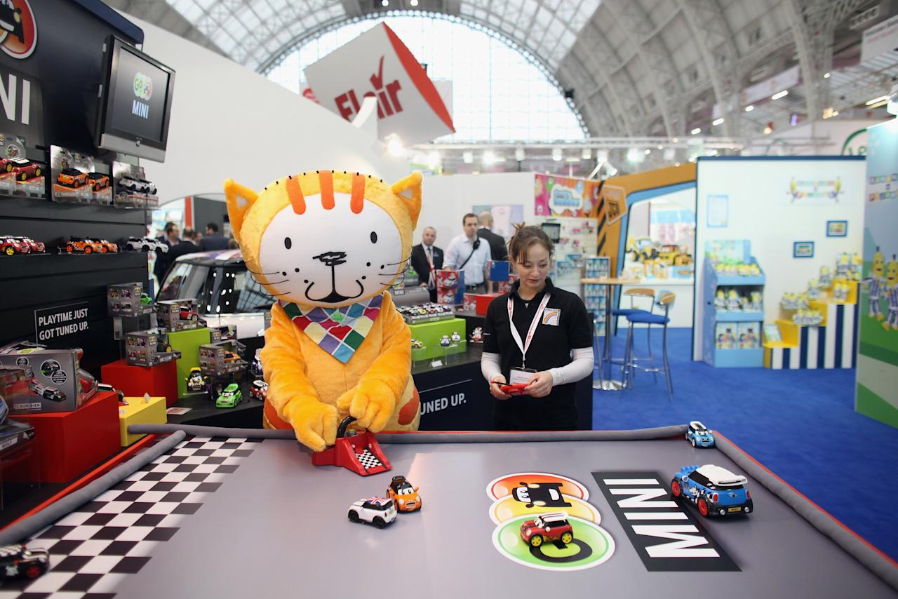 LONDON, ENGLAND - JANUARY 24:  A sales representative and toy character play with radio-controlled cars on display at  the 2012 London Toy Fair at Olympia Exhibition Centre on January 24, 2012 in London, England. The annual fair which is organised by the British Toy and Hobby Association, brings together toy manufacturers with retailers from around the world.  (Photo by Oli Scarff/Getty Images)