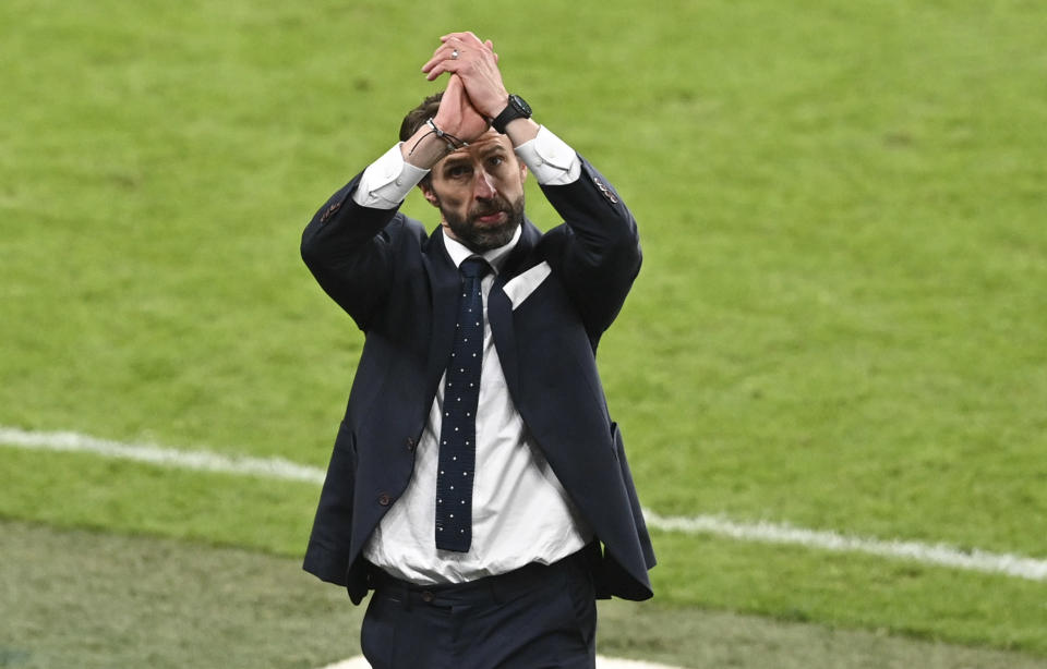 England's manager Gareth Southgate gestures to the crowd as England celebrate after defeating Denmark in their Euro 2020 soccer championship semifinal at Wembley stadium in London, Wednesday, July 7, 2021. (Justin Tallis/Pool Photo via AP)