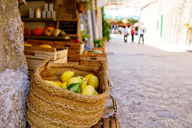 Ripe lemons for sale in a wicker basket in a picturesque village setting.