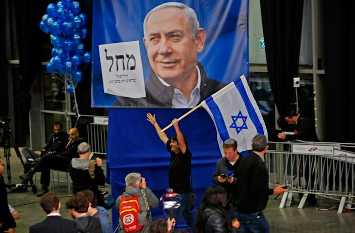 A man waves an Israeli flag in front of a giant Likud Party election poster of Prime Minister Benjamin Netanyahu at the Likud's electoral headquarters in the coastal city of Tel Aviv on March 2 after polls closed.