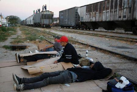 "Central American migrants rest next to the train tracks while waiting for the freight train ""La Bestia"", or the Beast, to travel to north Mexico to reach and cross the U.S. border, in Arriaga in the state of Chiapas January 10, 2012.  REUTERS/Jorge Luis Plata/File Photo"