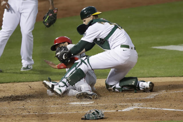 Oakland Athletics catcher Sean Murphy, right, tags out Los Angeles Angels' Jason Castro at home during the fourth inning of a baseball game in Oakland, Calif., Friday, July 24, 2020. (AP Photo/Jeff Chiu)