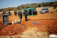 Farewell: A pastor reads a passage from the Bible at the funeral of coronavirus victim Modise Motlhabane as mourners stand at a distance