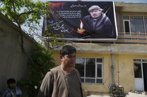 Ghulam Sakhi Allahdad, 38, stands under a poster bearing the image of his brother Wakil Hussain Allahdad, 32, one of the 57 victims of a suicide blast on a voter registration centre in Kabul, at Wakil's house in the city on April 23, 2018