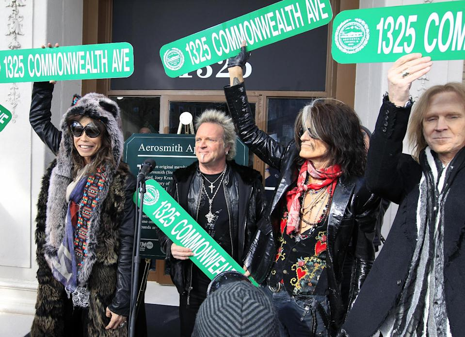 Aerosmith members, from left, Steven Tyler, Joey Kramer, Joe Perry and Tom Hamilton hold up signs Monday, Nov. 5, 2012 at an address in Boston's Allston neighborhood which was their home in the early 1970's. Aerosmith later gave a free concert in front of the building. (AP Photo/Elise Amendola)