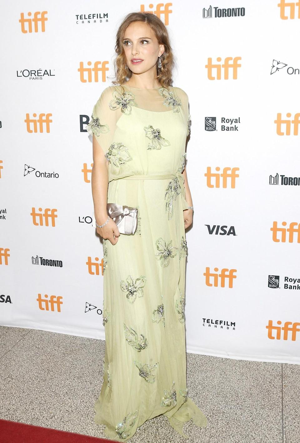 <p>Natalie cleverly covered up her bump in a draped lemon yellow Prada dress, embellished with a floral print at the Toronto Film Festival in September 2016. [Photo: Getty] </p>