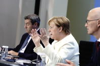 German Chancellor Angela Merkel, centre, Markus Soder, Prime Minister of Bavaria and CSU Chairman, left and Peter Tschentscher, the First Mayor of Hamburg, take part in a press conference, in Berlin, Tuesday, Sept. 29, 2020. Chancellor Angela Merkel and the governors of Germany's 16 states conferred on how to prevent the country's coronavirus infection figures from accelerating to the levels being seen in other European countries. (Kay Nietfeld/dpa via AP)