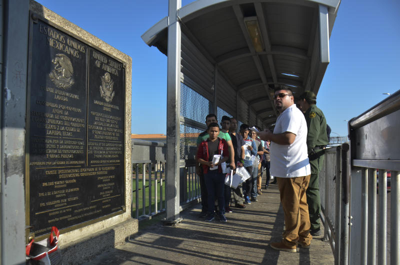 Mexican immigration agents receive a group of 21 Central Americans and two Cuban migrants being returned by U.S. Customs and Border Patrol officials under the so-called Remain in Mexico program for U.S. asylum seekers, on the international bridge between Laredo, Texas, and Nuevo Laredo, Mexico, Saturday, Sept. 14, 2019.(AP Photo/Salvador Gonzalez)