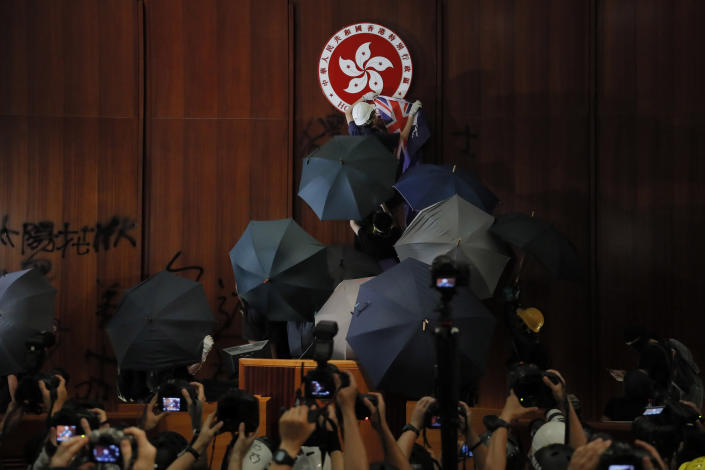 FILE - In this Monday, July 1, 2019, file photo, a protester covers the Hong Kong emblem with a Hong Kong colonial flag after they broke into the Legislative Council building in Hong Kong. Protesters smashed glass windows, sprayed rude graffiti and defaced Hong Kong's official emblem with black paint. But of all the dramatic photos showing hundreds of young protesters storming the city's parliament this week, one image makes for particularly uncomfortable viewing in Beijing: The British colonial flag draped aloft a podium in parliament's chamber. (AP Photo/Kin Cheung)